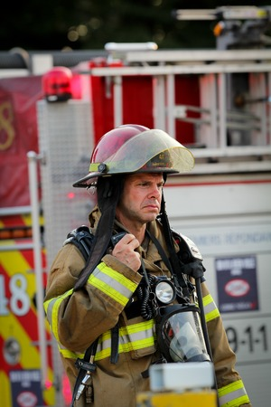 luitenant: MONTREAL, CANADA - AUGUSTUS 01: Luitenant brandweerman voor brandweerwagen op een brand ter plaatse, praten over de walkie op 1 augustus 2014 in Montreal Redactioneel
