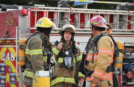 luitenant: MONTREAL CANADA - AUGUSTUS 01: Unidenfity luitenant brandweerman in de voorkant van brandweerwagen voorbereiding van de implementatie op 1 augustus 2014 in MONTREAL Redactioneel