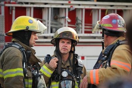 luitenant: MONTREAL CANADA - AUGUSTUS 01: Unidenfity luitenant brandweerman in de voorkant van brandweerwagen bespreken met de brandweer op 1 augustus 2014 in Montreal