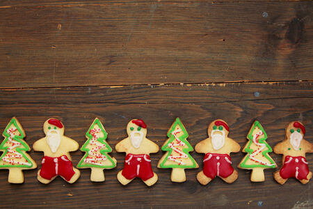 Santa claus and christmas tree cookies on a wooden table photo