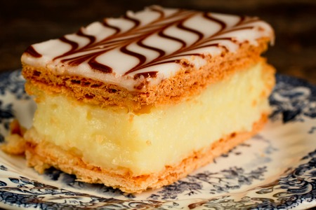 napoleon dessert: Millefeuille, french pastry with custard in a blue plate and wooden table