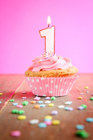 1: Number one birthday candle on a pink cupcake on a wooden table