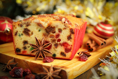 dry fruits: Traditional fruit cake for christmas with anise, cinnamon and dried cranberries with christmas background Stock Photo