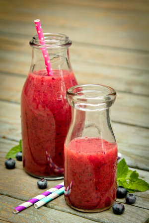 Blueberry smoothie with fresh fruits and straw on a rustic wood photo