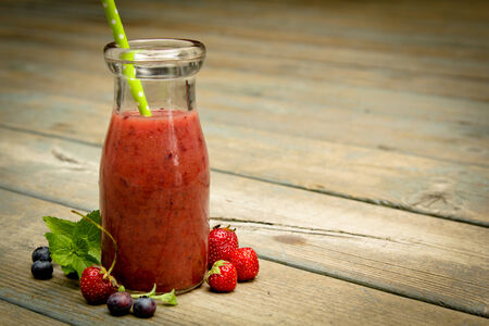 Berry smoothie with fresh fruits on a rustic wood photo