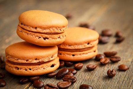 Three coffee macarons on a table with coffee beans photo