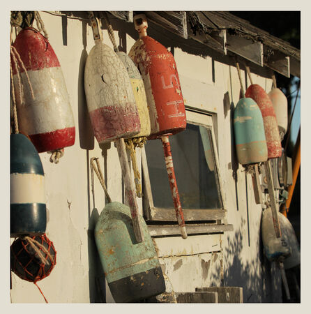 floats: Old buoys on a wall on a shack in Maine, USA.  Cross processed to look like and instant picture.