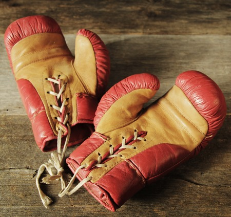 padding: Retro pair of red and yellow boxing gloves on a table.
