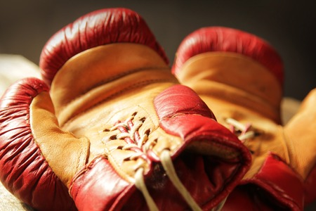 padding: Retro pair of red and yellow boxing gloves lying on a table. Stock Photo