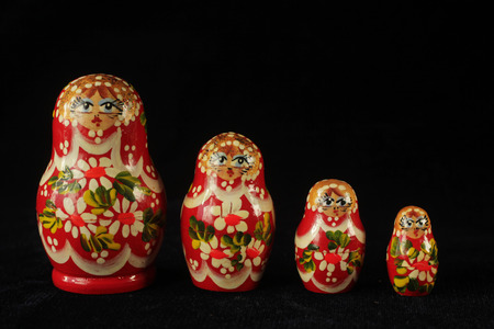 Traditional russian dolls in a row on a black background