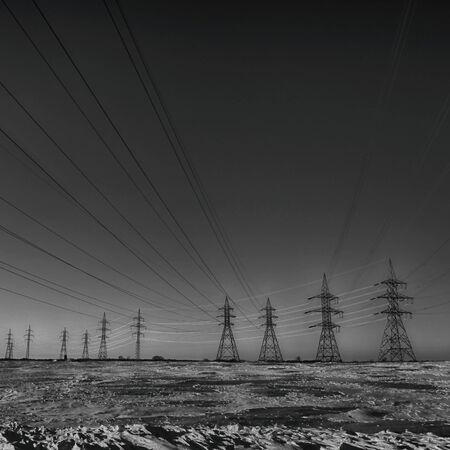 electric power station: Group of high-voltage electricity power pylons in black and white and snow covered countryside, Canada