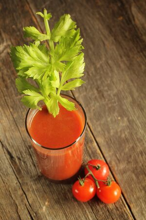 Tomato juice with celery branch on a wooden background photo