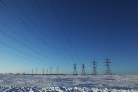 electricity grid: Group of high-voltage electricity pylons power over blue sky and snow covered countryside, Canada
