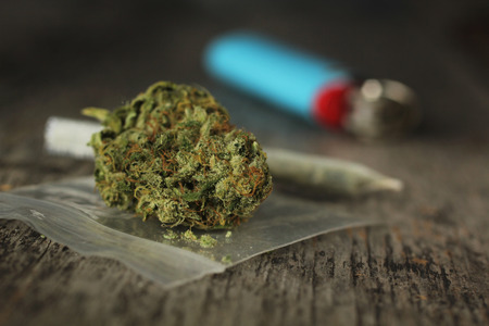 Closeup of marijuana joint and buds and blue lighter on a wooden table with a shallow depth of field Stock Photo