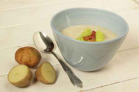 Potato soup in a blue bowl with fresh potatoes and spoon on a white wooden background