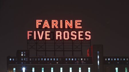 industrial heritage: MONTREAL CANADA JANUARY 25, 2015: Icon of the industrial heritage of Montreal, neon Flour five roses illuminated Montreal since 1948. In 2006, the new owner of the building saved it from the destruction. Editorial