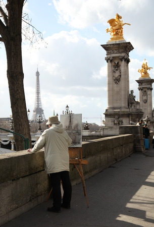 PARIS, FRANCE - MARCH 04, 2014: Old man artist drawing the Eiffel tower along the seine river in Paris, France.