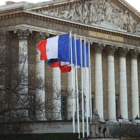 Assemble national is the lower house of the bicameral Parliament of France under the Fifth Republic.  French flags floatings in front of the assemble.