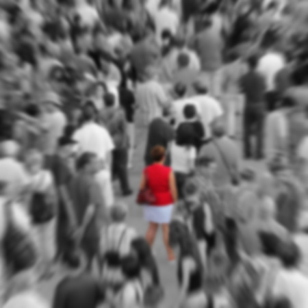 paranoia: Blur background showing woman in red in a middle of a crowd in black and white.