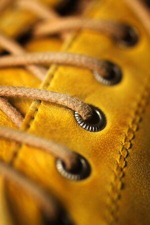 Close up of eyelet and lace was yellow leather shoe. Only the middle eyelet in focus.