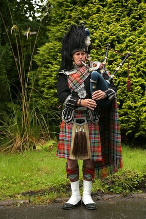 bagpipes: EDINBURGH, SCOTLAND - JULY 28 2015 : Unidentified Scottish Bagpiper playing music with bagpipe in Scotland.  Bagpipes are a class of musical instrument, aerophones, and have been played for centuries. Editorial