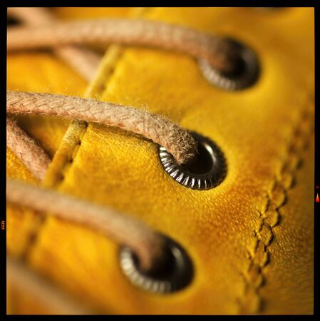 eyelet: Close up of eyelet and lace on a leather yellow shoe.  Only the middle eyelet in focus. Stock Photo