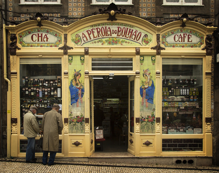 open trench: PORTO-PORTUGAL NOVEMBER 4, 2015: Two old men looking a window in a little cafe and store in Porto, Portugal