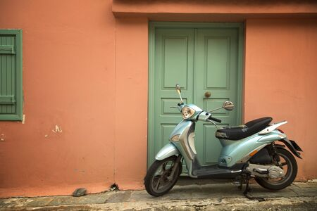 Blue scooter on a peach wall with green door Stock fotó