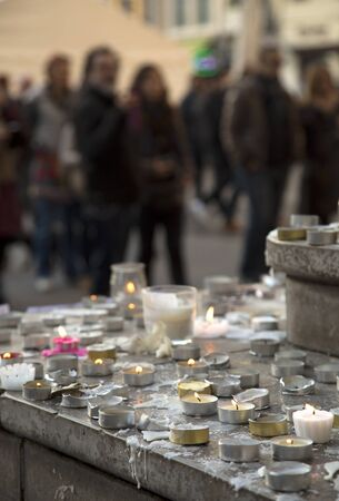 happens: LYON-FRANCE NOVEMBER 15, 2015: People praying and giving offerings, flowers and lighting candles on the steps of the town hall at Lyon, France about the terrorist bombing happens in France on 13th november 2015.