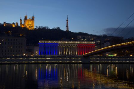 france: The historic courthouse of Lyon with the colors of France flag with  Basilica of Fourviere over the soane in background at sunset.