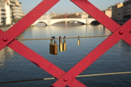 padlocks: Three padlocks on a red bridge in Lyon, France Stock Photo