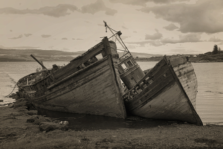 ship wreck: Two old wooden boats aground on isle of Mull, Scotland. Sepia.