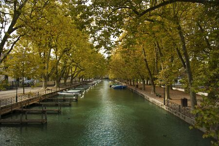 riverside trees: Pier and yellow trees at the riverside in Annecy, France during fall season