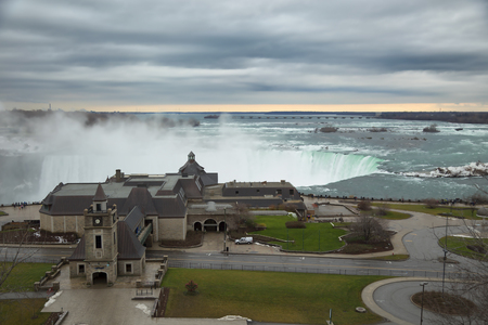 horseshoe falls: View of the horseshoe falls from canadian border and welcome center building at Niagara falls during winter season