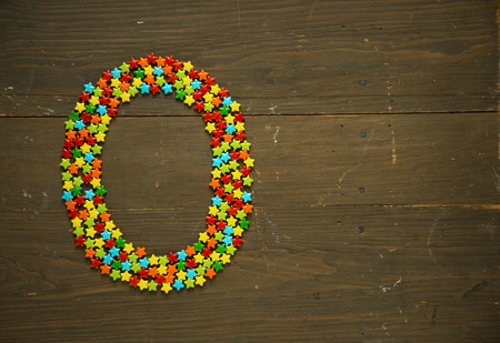 Letter O from alphabet made with star shape candy on a wooden background Banco de Imagens