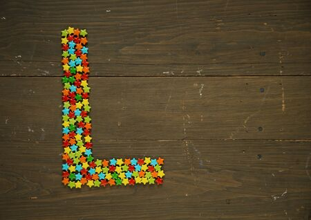 solid background: Letter L from alphabet made with star shape candy on a wooden background