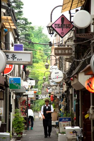 TOKYO-JAPAN, 19 June 2016: People walking through a small alley in the Golden Gai area in Shinjuku, Tokyo, Japan.  famous both as an area of architectural interest and for its nightlife. 新聞圖片
