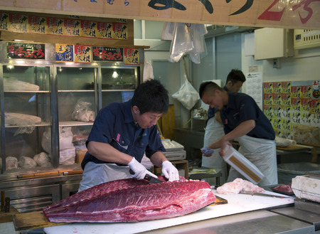 overfishing: TOKYO-JAPAN, 27 June 2016: Man preparing tuna fish at the fish market in Tokyo, Japan.  It is the biggest wholesale fish and seafood market in the world.