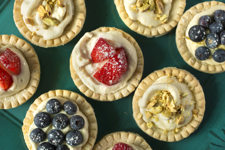 Blueberry, strawberry and pistachios tarts in a green tray  写真素材