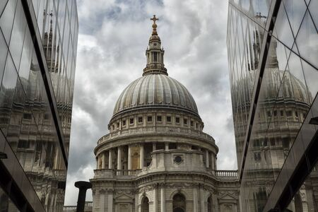 St-Pauls Cathedral and reflection in a mirror wall with a cloudy sky Stock Photo