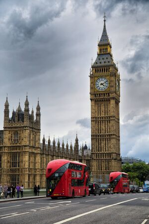 busses: LONDON, UK - MAY 29, 2017:  Red busses in front of Big Ben, nickname of the Great Bell of the clock at the north end of the Palace of Westminster in London