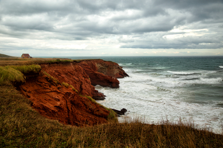 Red cliff in Havre Aubert with the ocean Imagens