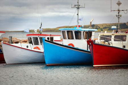 Blauwe, witte en rode vissersboten op de pier in Havre Aubert in Quebec, Canada Stockfoto