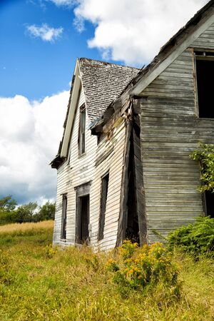 Side view of a derelict house in a middle of a field Stock Photo