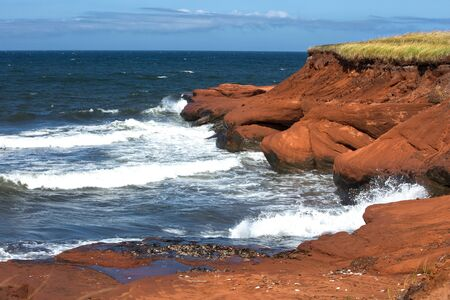 Red cliff in Cap aux Meules with waves in the ocean in the St-Lawrence golfe in iles de la madeleine in Canada