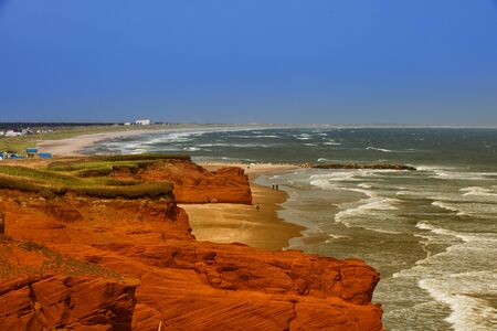 Red cliff in Havre aux maisons with the ocean Imagens