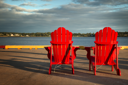 2 red Adirondack chairs in front of the ocean in Prince Edward island  Stock Photo