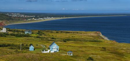 Beautiful blue house by the sea.  Rugged cost line of Havre Aubert in magdalen island in Quebec, Canada Imagens