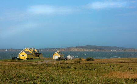 Beautiful yellow house by the sea.  Rugged cost line of Havre Aubert in magdalen island in Quebec, Canada