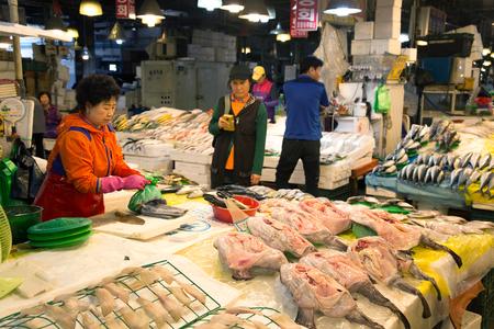 SEOUL-SOUTH KOREA, MAY 18, 2018: Woman at her booth at the fish market in south Korea. Noryangjin Fish Market is an extensive farmers market in Noryangjin-dong